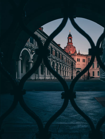 Historic building seen through fence in city during sunset
