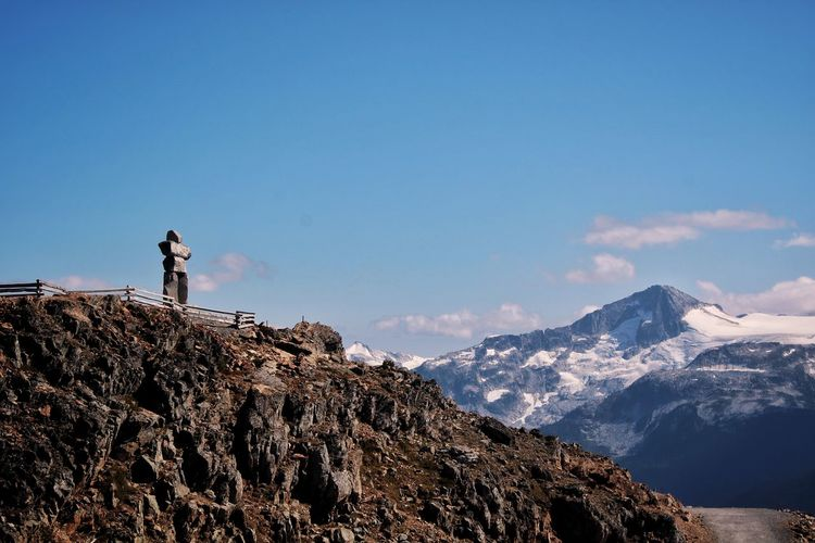Scenic view of snowcapped mountains against sky and famous whistler inukshuk