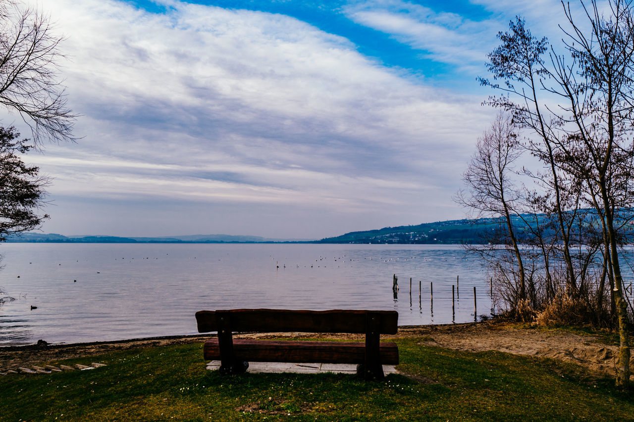 Empty Bench At Lakeshore Against Sky