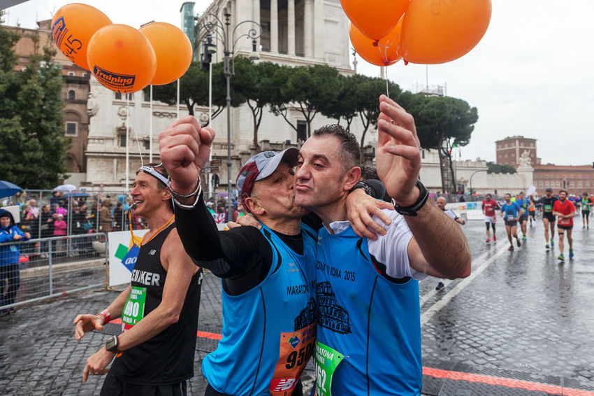 Rome, Italy - March 22, 2015: two participants in the Rome Marathon 2015 hug on arrival after traveling less than 42 km street circuit in the rain. Athlete Atletic Competition Day Gay Happiness Happy People Italy Marathon Outdoors Rain Rome Runners Running Smack Street Running Water
