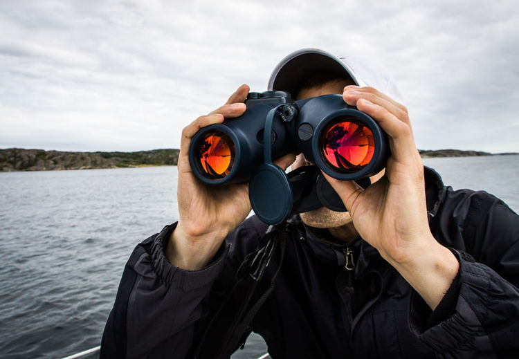 Man Looking Through Binoculars In Sea Against Cloudy Sky