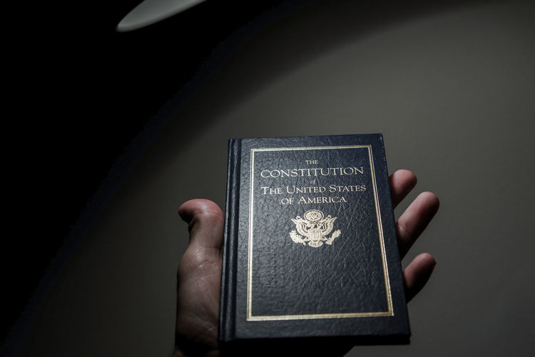 Hand holding a The Constitution of The United States of America under a lamp. Dark Human Rights Politics Rights United States America Constitution Hand Holding Lamp Night Symbolic  Symbolism Vote Voting