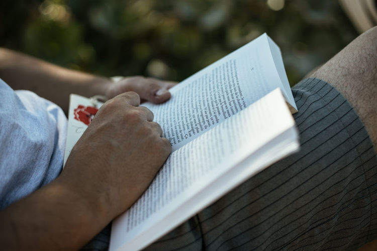 Low section of man reading book