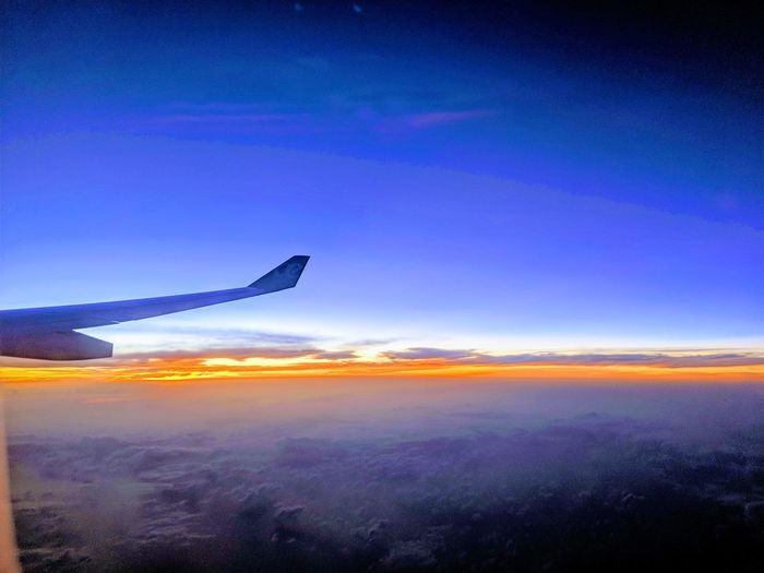 Airplane flying over cloudscape during sunset