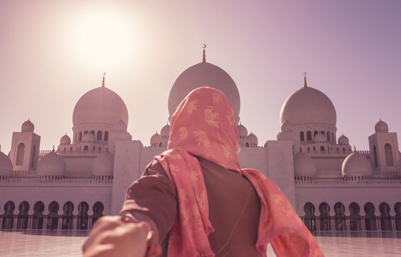 Cropped image of man holding woman hand at sheikh zayed mosque during sunny day