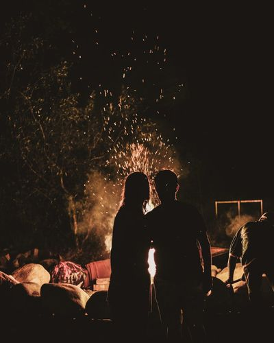 Silhouette man and woman standing by bonfire at night