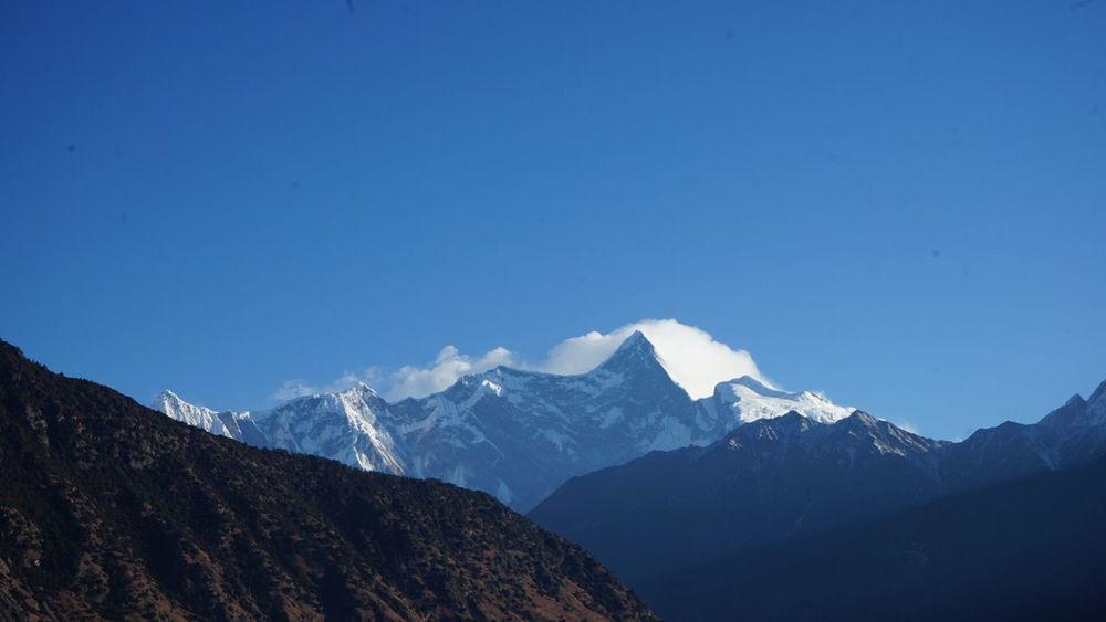 """南迦巴瓦峰,是中国西藏林芝地区最高的山,海拔7782米。为西藏最古老的佛教""""雍仲本教""""的圣地,有""""西藏众山之父""""之称。同时,紧邻着的雅鲁藏布大峡谷绕着他转了一个马蹄形的弯,随后通向印度洋方向延伸出去。 南迦巴瓦峰它还有另一个名字""""木卓巴尔山"""",其巨大的三角形峰体终年积雪,云雾缭绕,从不轻易露出真面目,所以它也被称为""""羞女峰""""。南迦巴瓦在藏浯中有多种解释,一为""""雷电如火燃烧"""",一为""""直刺天空的长矛',还有一为""""天山掉下来的石头""""。后一个名字来源于《格萨尔王传》中的""""门岭一战"""",在这段中将南迦巴瓦峰描绘成状若""""长矛直刺苍穹""""。"""