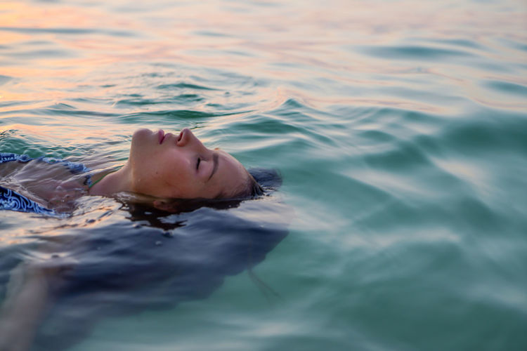 Woman swimming in the sea at sunset