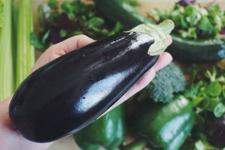 hand holding an eggplant other vegetables in the background Eggplant Vegetable Vegetarian Food Vegetarian Food Vegetarian Vegetables & Fruits Vegetarian Vegetables & Fruits Hand Human Body Part Human Hand Freshness Healthy Eating Human Hand Close-up