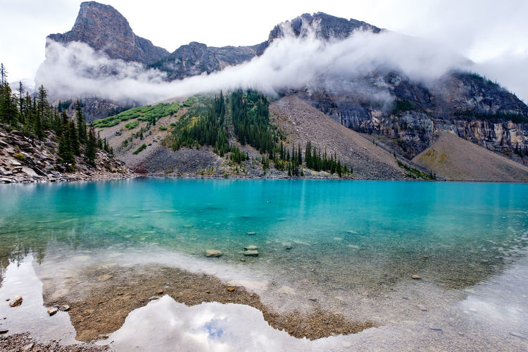 A reflection of surrounding mountains covered by fog at Moraine Lake, Banff National Park, Alberta, Canada. Water Beauty In Nature Mountain Scenics - Nature Tranquil Scene Tranquility Nature Lake Day Sky No People Non-urban Scene Idyllic Land Geology Turquoise Colored Hot Spring Power In Nature Outdoors Banff National Park  Banff  Banff Alberta Moraine Moraine Lake  Water Reflection 17.62° Stay Out