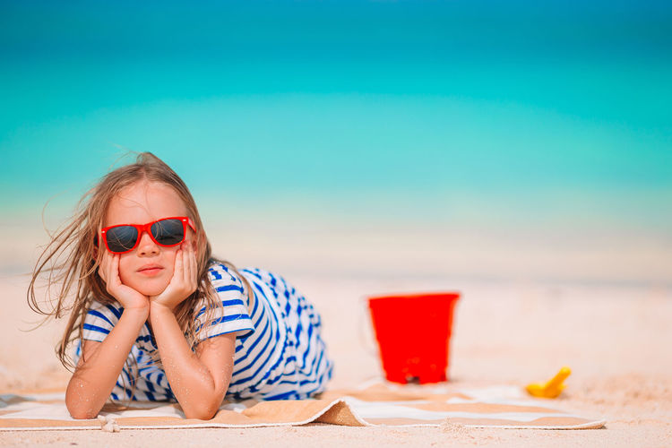 Woman wearing sunglasses on table at beach
