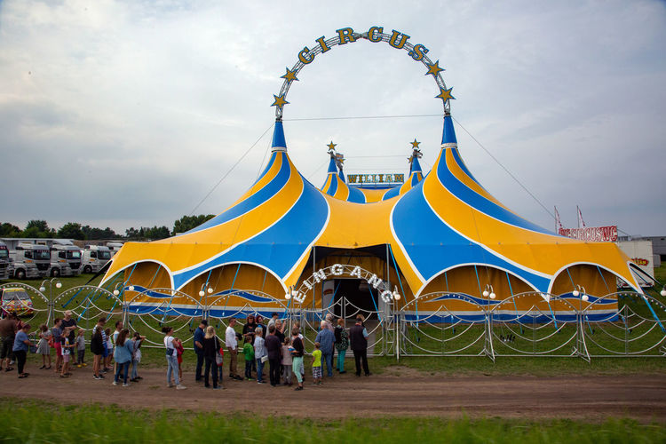 Circus Adult Architecture Arts Culture And Entertainment Building Exterior Built Structure Cloud - Sky Crowd Day Group Of People Large Group Of People Lifestyles Men Nature Outdoors Real People Sky Travel Destinations Women Yellow