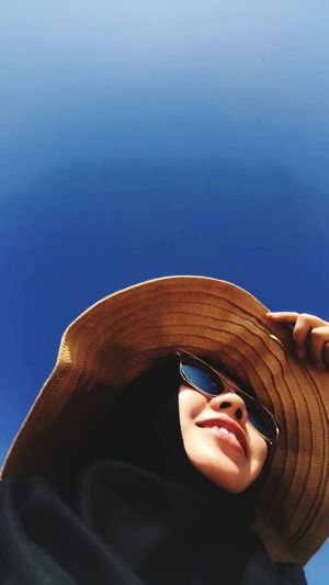 Close-up of woman wearing sunglasses and hat against clear sky