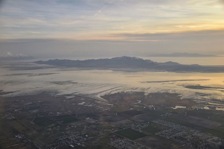 Aerial view from airplane of Antelope Island at sunset, view from Magna, sweeping cloudscape at sunrise with the Great Salt Lake State Park in winter. USA, Utah. Scenics - Nature Cloud - Sky Sky Tranquil Scene No People Nature Salt Lake Salt Lake City Antelope Island Antelope Island State Park Airplane Drone  Sunset Winter