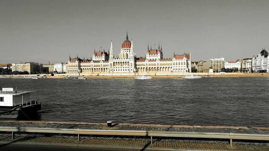 Hungarian Parliament Building By Danube River Against Clear Sky
