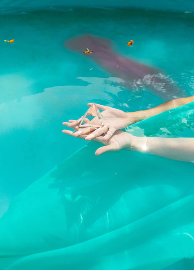 Cropped hands of woman holding prism in swimming pool