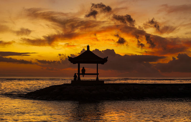 Silhouette of a gazebo with people hanging out at the gazebo . Dramatic clouds and orange sky during sunrise or sunset. Dramatic Sky Gazebo Gazebo On The Beach Architecture Beach Beauty In Nature Built Structure Cloud - Sky Day Horizon Over Water Idyllic Landscape Nature No People Orange Color Outdoors Scenics Sea Silhouette Sky Sunrise Sunset Tranquil Scene Tranquility Water