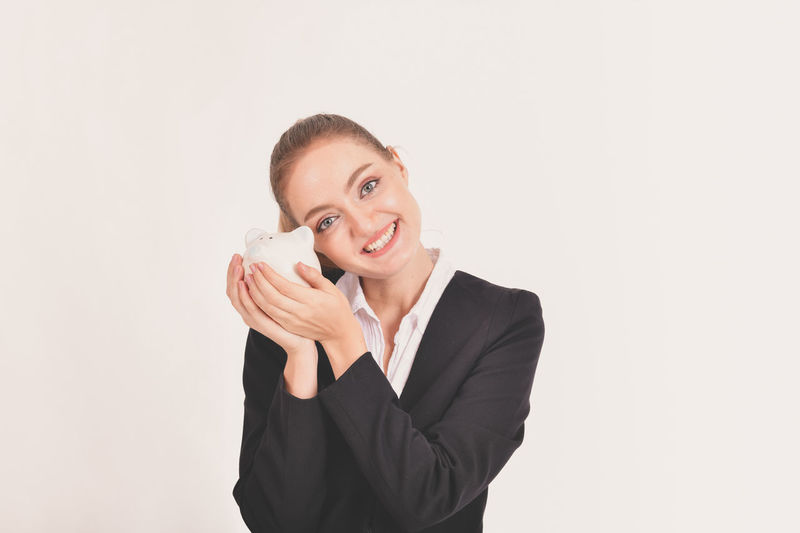 Businesswoman Copy Space Cut Out Emotion Front View Happiness Holding Indoors  Looking At Camera One Person Portrait Smiling Studio Shot Suit Waist Up White Background Women Young Adult