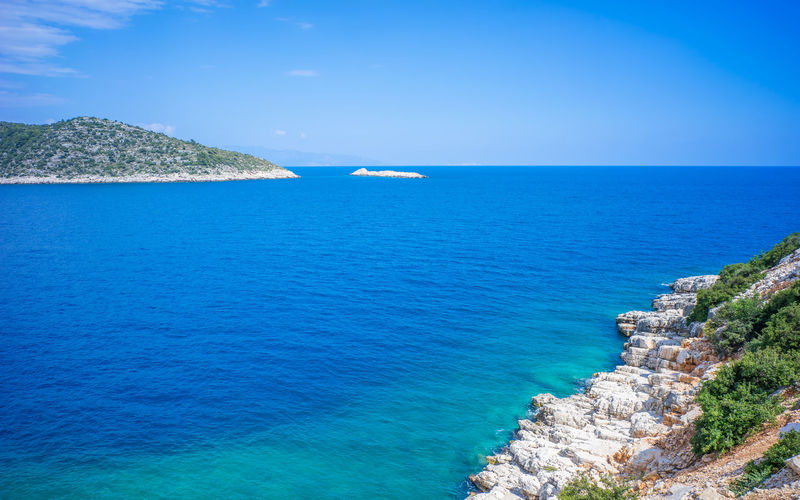 Dark blue Aegean Sea inlet under blue sky in summer. Taken at Road D400, the famous self-driving route in Turkey for tourists, opposite Kas peninsula. Aegean Attraction Bank Blue D400 Drive Inlet Kas Peninsula Road Rock Rough Seascape Sky Summer Tourism Travel Turkey Visit Water