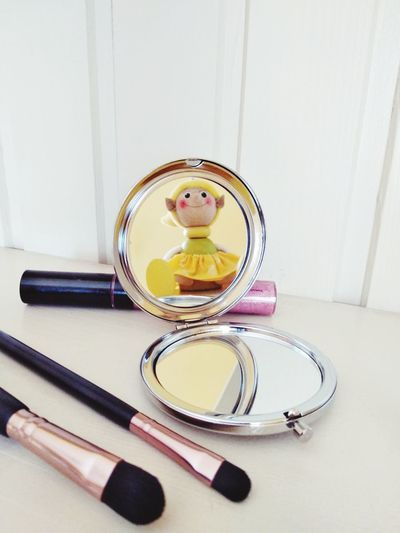 Close-Up Of Beauty Product And Hand Mirror On Table