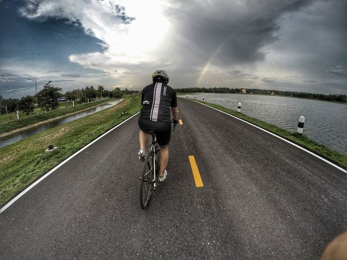 Rear view of man cycling on road by river against cloudy sky