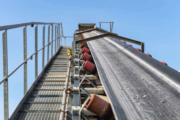 Close-up shot of the conveyor belt in the concrete plant with transport rollers,  metal stairs.