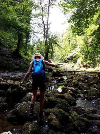 Women Hicking Backpack Blue Hat Summer Sports Water Tree Full Length Men Adventure Sky Ankle Deep In Water Shallow Clear Stream Muddy Wet Rolled Up Pants Wading