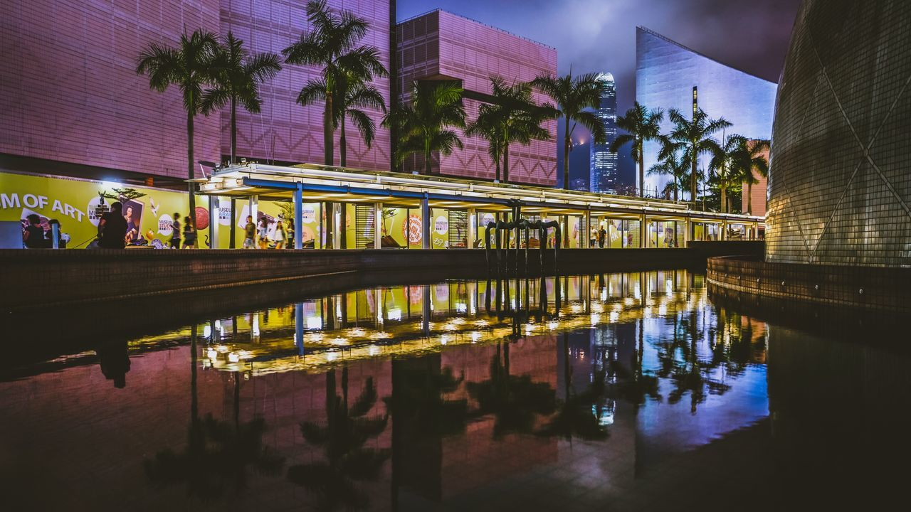 Reflection Of Illuminated Buildings In Pond At Dusk
