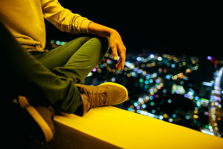 Low section of man sitting at balcony against illuminated city at night