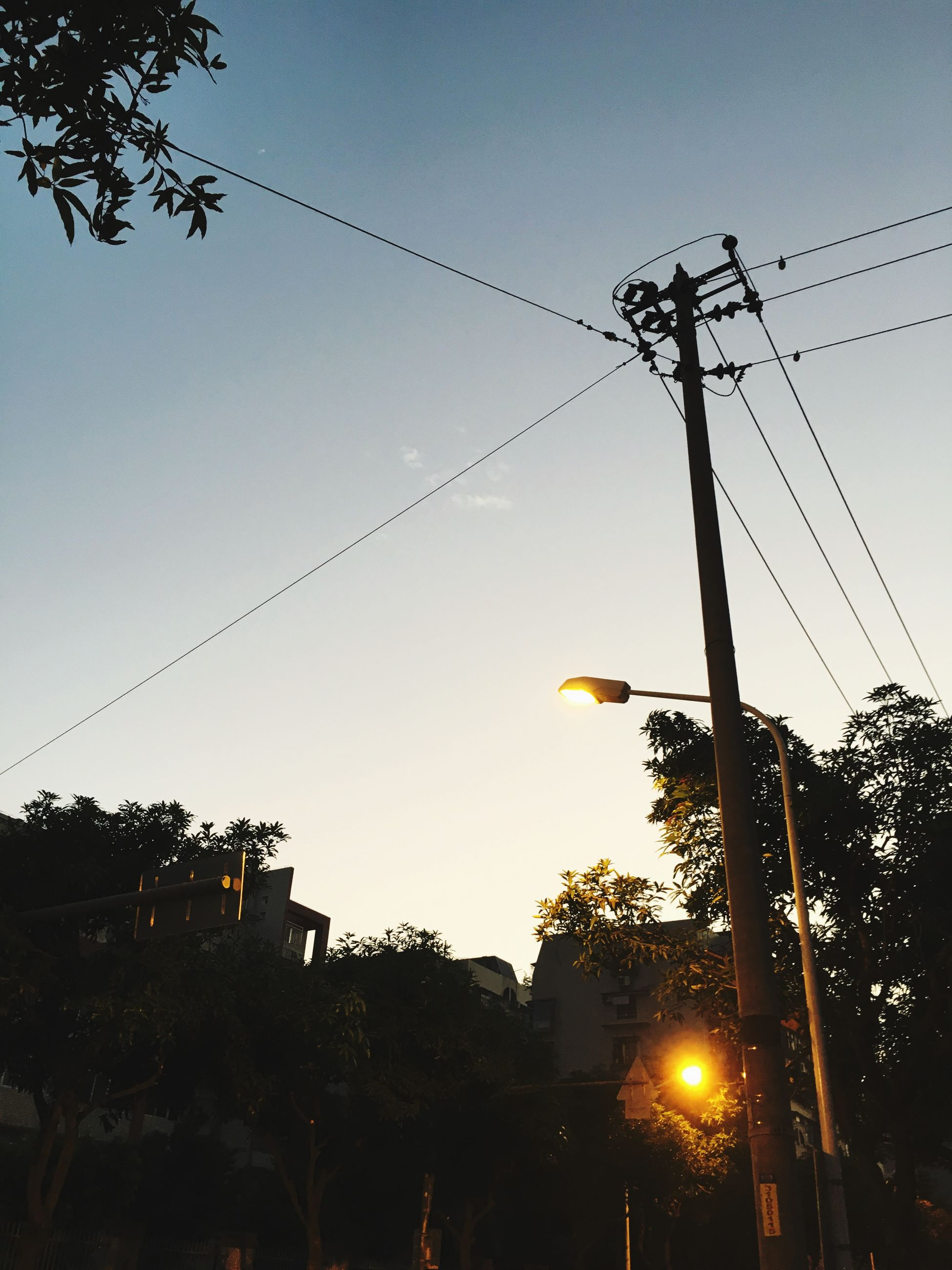 power line, electricity pylon, cable, low angle view, sunset, clear sky, electricity, silhouette, tree, building exterior, built structure, architecture, power supply, street light, sky, fuel and power generation, dusk, house, connection, lighting equipment