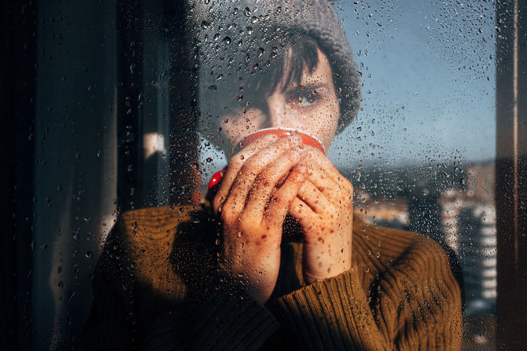 Portrait of woman seen through wet window in rainy season