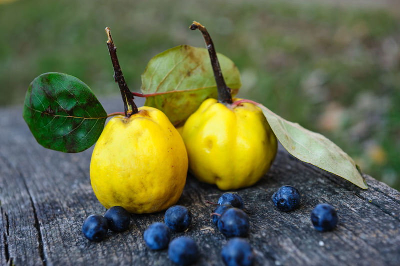 Close-up of quinces with blueberries on wooden table