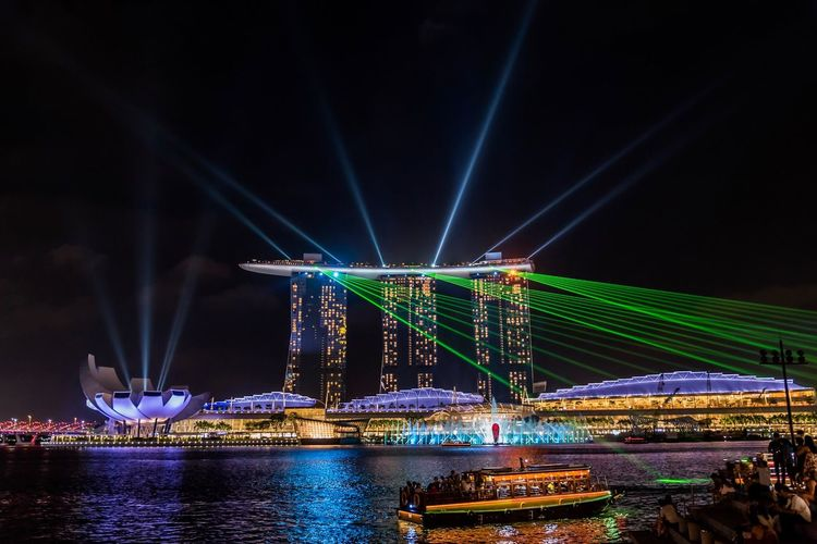 Let the show begins! The Marina Bay Sands Light and Water Show is one show that you can watch in Singapore every night for free. Marina Bay Sands Singapore Illuminated Night Water Built Structure Architecture Travel Destinations Transportation Travel Nightlife