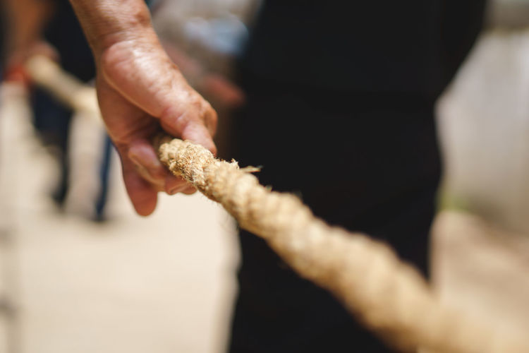 Close-up of hand holding rope
