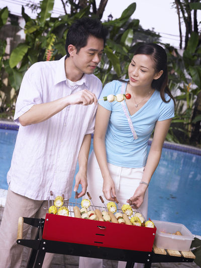 Young man showing food to woman while grilling against swimming pool