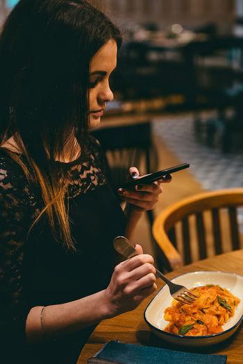 Woman holding ice cream in restaurant