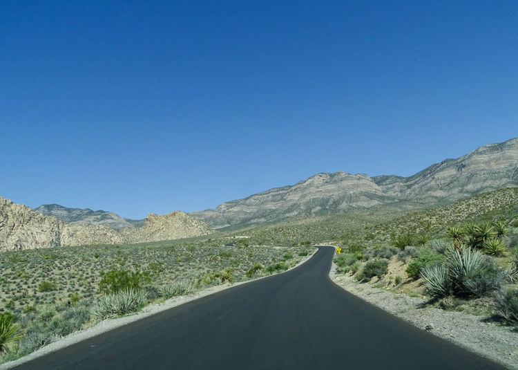 Road amidst mountains against clear blue sky