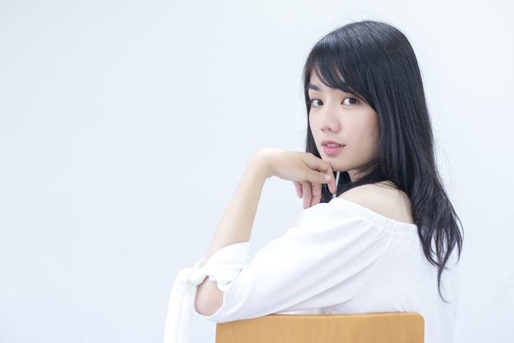 Portrait Of Young Woman Sitting Against White Background