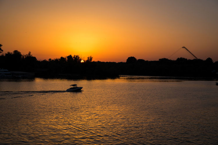 Silhouette person on river against sky during sunset