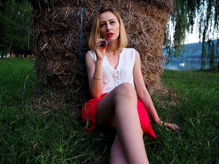 Beautiful woman smoking cigar while sitting on grassy field against hay