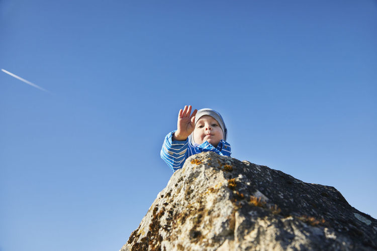 Low angle view of woman standing on rock against clear blue sky