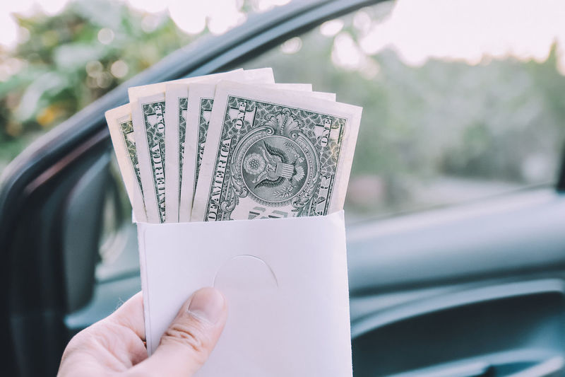 Cropped hand holding paper currency against car