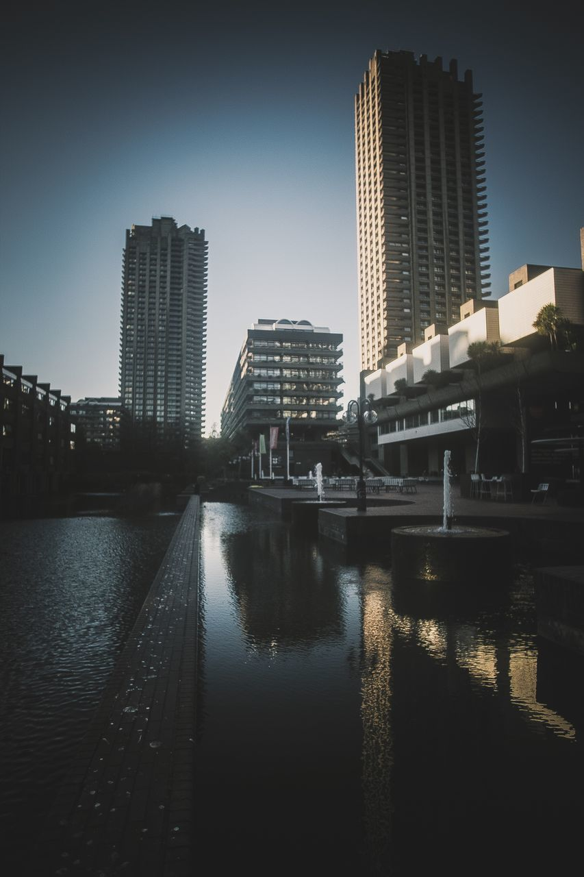 architecture, built structure, skyscraper, building exterior, city, modern, water, reflection, travel destinations, river, outdoors, bridge - man made structure, no people, downtown district, clear sky, cityscape, day, urban skyline, sky