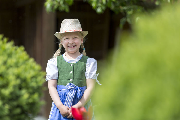 Portrait of girl smiling while standing outdoors