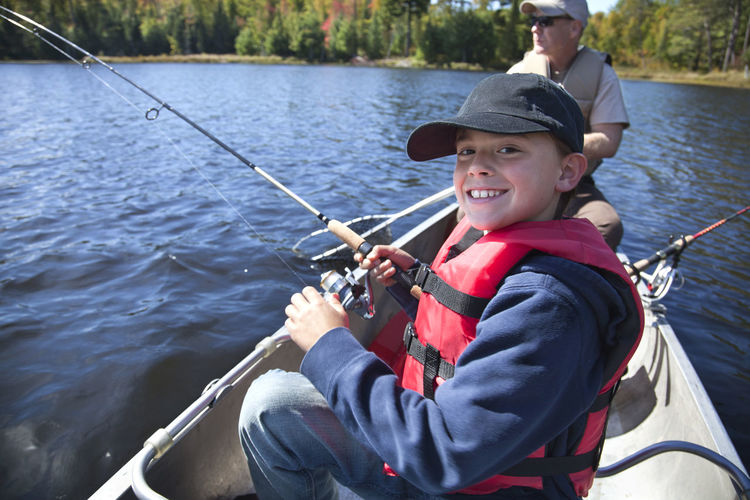 Young boy smiles as he reels in a walleye on a Minnesota lake Boy Child Fishing Smiling Fisherman Man Dad Father Happy Lake Walleye Fish Minnesota USA Canoe Boat Water Pines Trees North Stringer Catch Outdoors Recreation  Fun Color Image Photography People Sunlight Life Preserver Autumn Hat Cap Sunglasses Young Fishing Rod
