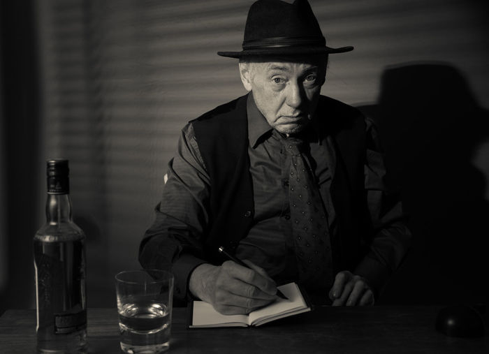 Film Noir reloaded: The dirty old detective in his bureau talking to a new client Acting Adult Hat Adult Alcohol Bottle Detective Drinking Glass Front View Hat Indoors  Monochrome Old Person Old Person Sitting One Man Only One Person People Portrait Real People Sitting Studio Shot Table