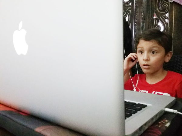 Bewildered kid watching movie on laptop computer 7 Years Old Astonished Bewildered Boy Caucasian Computer Internet Addiction Earphones Expression Holding Indoors  Kid Laptop Leisure Activity Lifestyles Listening Mac MacBook Pro Portrait Staring The Portraitist - 2016 EyeEm Awards Watching A Movie Young Tech Technology