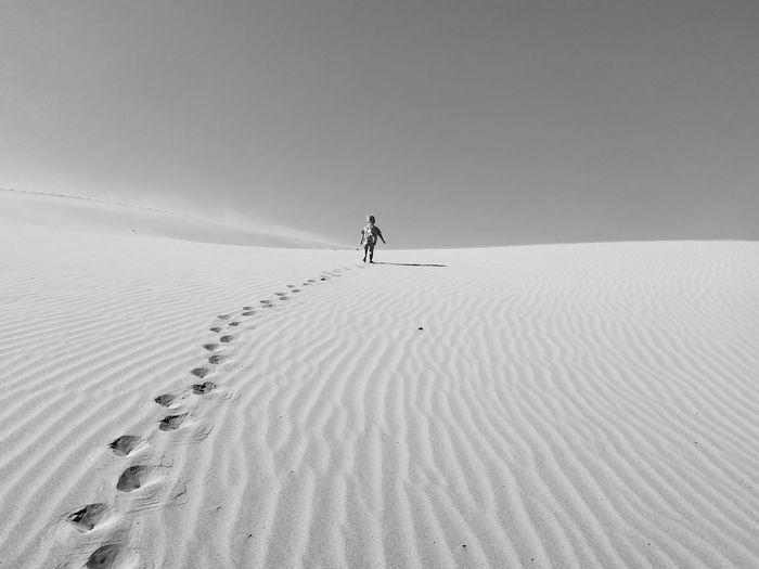 Toddler walking on desert against sky during sunny day
