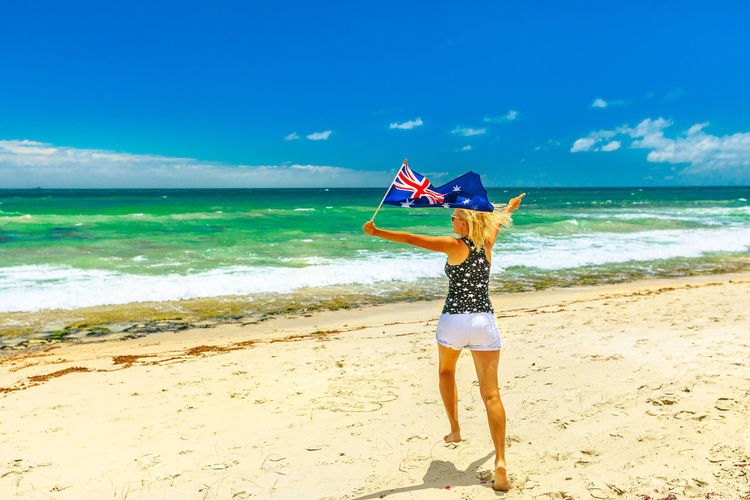 Rear view full length of woman holding australian flag running at beach