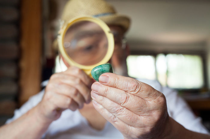 old man inspecting a precious stone Blurred Close-up Enlarge Evaluation Experienced Eye Fingers Gemstones Glasses Green Holding Human Hand Jeweler Jewelry Looking Magnifier Magnifying Glass Nature Precious Gem Satisfaction Semi Precious Stones Shape Size Value Weight